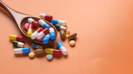 suplementy : Multi colorful pills and capsule on spoon on color background