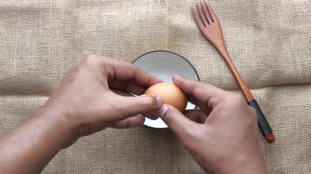 abriu : top view of man hand processing egg in a bow Vídeos