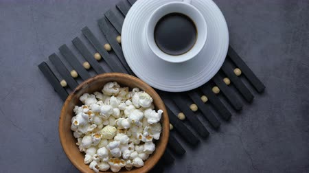 markalaşma : Close up of popcorn in a bowl and tea on table Stok Video