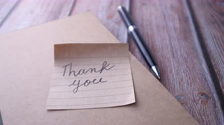 dankbaar : Close up of thank you note on notepad Stockvideo