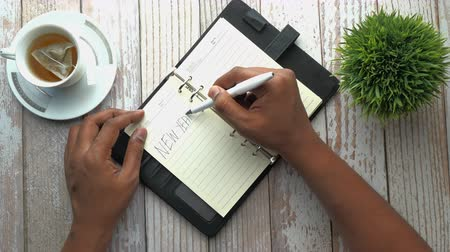 plano : top view of man hand writing new year goals on notepad