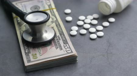 Close up of cash, pill and stethoscope on table