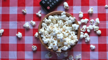 попкорн : Popcorn, TV remote on a table. concept of watching movies at home.