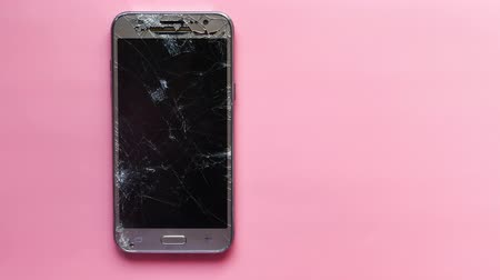 top view of broken smart phone on pink background