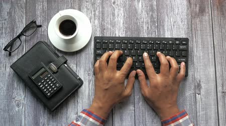top view of man hand typing on keyboard on office table
