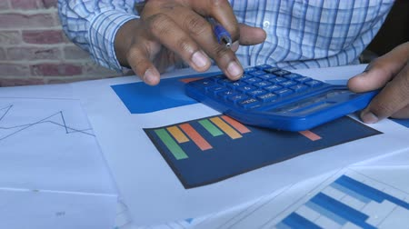 close up of person using calculator and analyzing charts Vídeos
