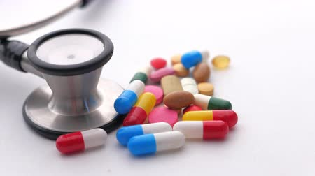 Close up of pills and stethoscope on white background