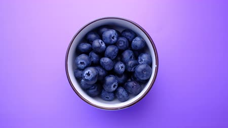 top view of blue berry in a bowl on purple background Wideo