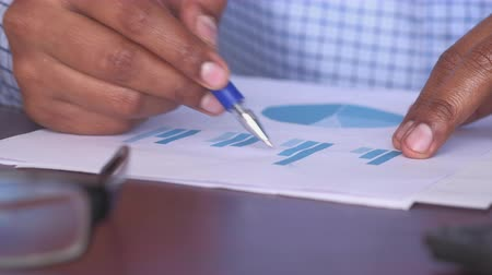 close up of person hand analyzing chart on office desk Wideo
