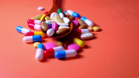 close up of colorful pills on spoon orange background