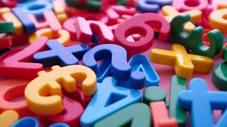 colorful alphabet on a pink background , close up