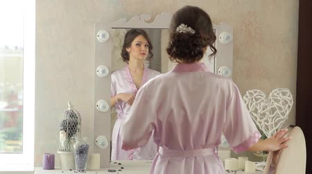 admires : The girl stands in the mirror. Looking at herself in the mirror. Admires. Beautiful, stylish environment. Stylish design. The girl adjusts her hair.