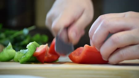 zöldségek : Close-up of chefs hands chopping green & red peppers for cooking