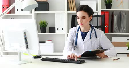 doctor typing text on keyboard in white office. Dostupné videozáznamy