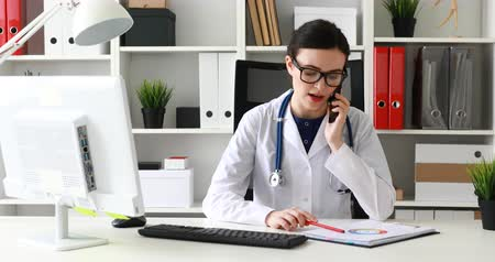 doctor in glasses calls on phone at the workplace.