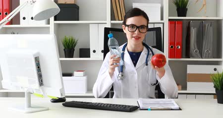 doctor holding bottle of water and red apple in hands and explaining.