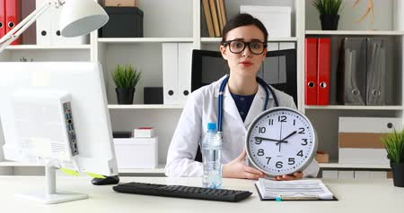 doctor holding clock in hand and holding out bottle of water at camera.