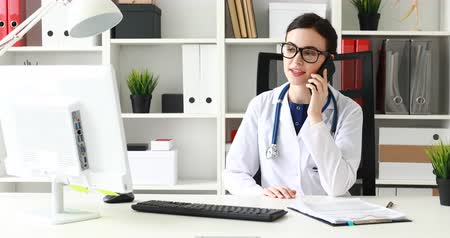 doctor talking on phone and looking at monitor