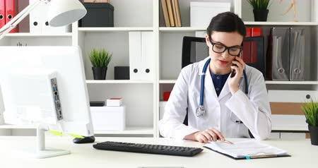 doctor talking on phone and looking in documents Dostupné videozáznamy