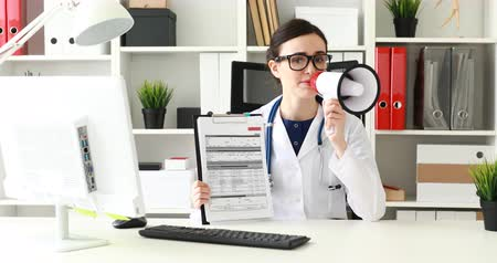 doctor speaking in loudspeaker and showing documents while in office.