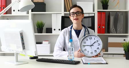 Doctor with large clock stretching bottle of water on camera