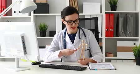 doctor showing body parts on wooden model of man. Dostupné videozáznamy