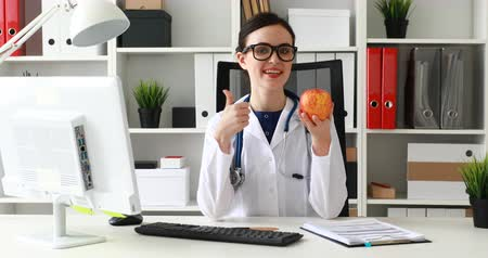 doctor in white lab holding apple in hand and showing thumb up Dostupné videozáznamy