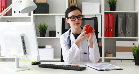 doctor sitting at table, looking at red apple and making gesture okay Dostupné videozáznamy
