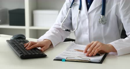 Cropped image of female doctor typing on keyboard