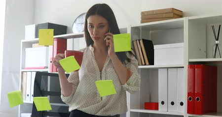 businesswoman in white blouse considering stickers on glass and talking on phone Dostupné videozáznamy