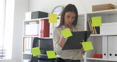 businesswoman making notes in documents standing near glass wall