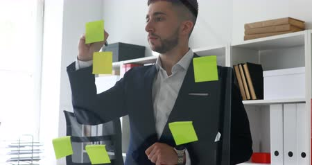 businessman making notes in stickers on glass wall