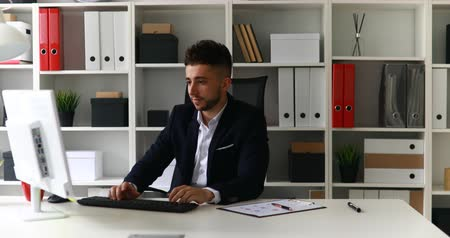 young businessman working on computer and leaning back in office-chair