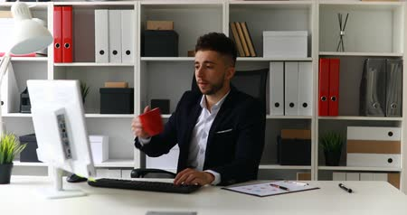 vazo : young businessman working on computer and drinking coffee