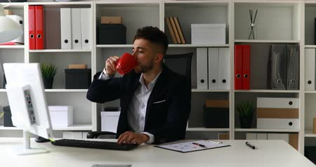 young businessman working on computer and drinking coffee