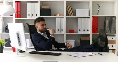 young businessman working with legs on table in office