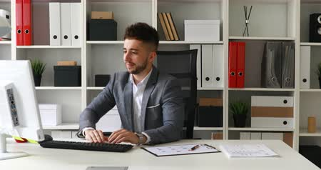 young businessman spinning in office-chair rejoicing at success