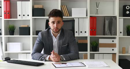 young adult businessman in workplace looking at camera in modern office
