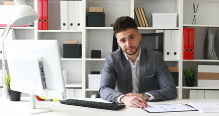 young businessman in workplace looking at camera