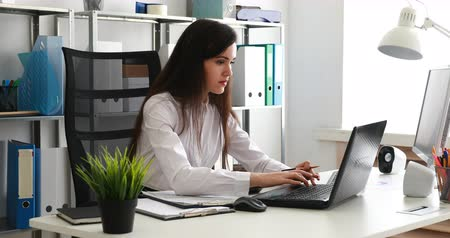 businesswoman working on laptop and writing on paper in modern office