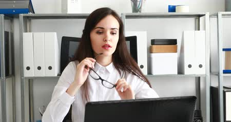 businesswoman taking off black glasses and working on laptop in modern office Dostupné videozáznamy