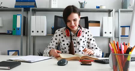 woman with red headphones on shoulders closing book and leaning back