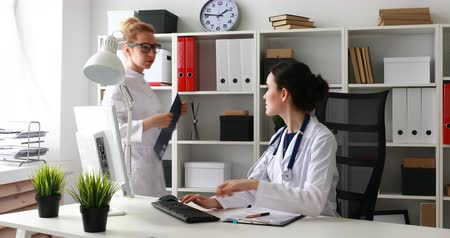 на камеру : doctors discussing schedules on paper in office