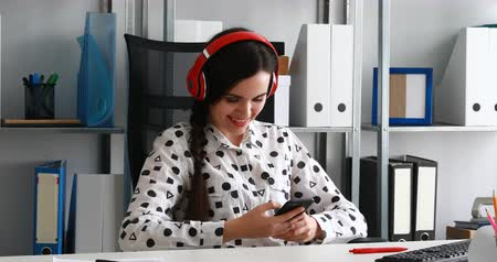 moderní : businesswoman in headphones using smartphone in modern office
