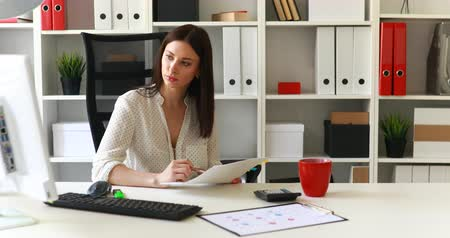 flowerpots : businesswoman sitting in office-chair and looking in documents Stock Footage