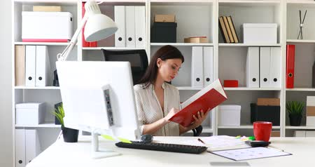 bureaulamp : businesswoman in white blouse examining documents in folder Stockvideo