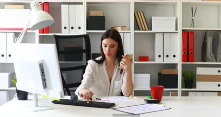 vazo : businesswoman working at computer and using smartphone in light office