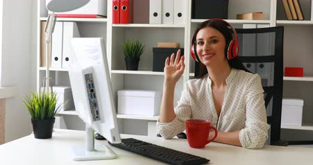 paper airplane : businesswoman listening music, looking to monitor and waving hand at camera