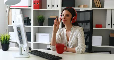 flowerpots : businesswoman listening music, looking to monitor and waving hand at camera