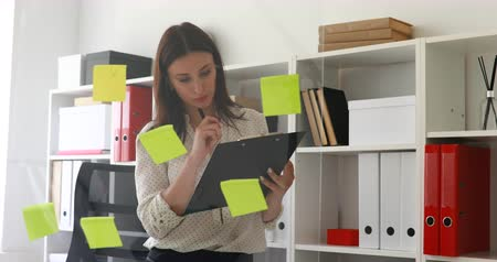 blouse blanche : businesswoman making notes in documents standing near glass wall